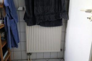 Heizkörper teilweise verdeckt durch ein Handtuch